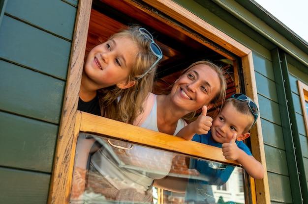 Moeder en haar kinderen kijken uit het raam van een trein