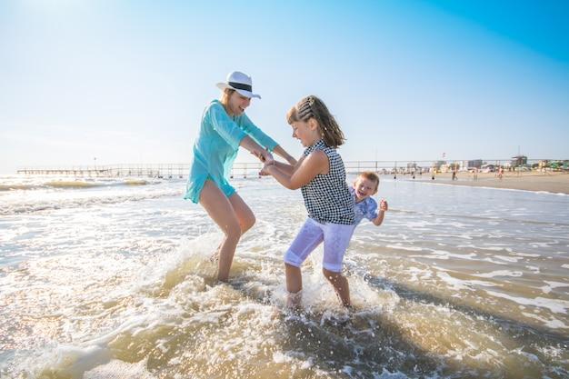 Moeder en haar kinderen spelen in de zee