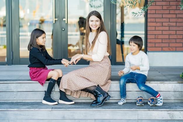 Moeder en haar kinderen spelen met de hand met een glimlach buitenshuis