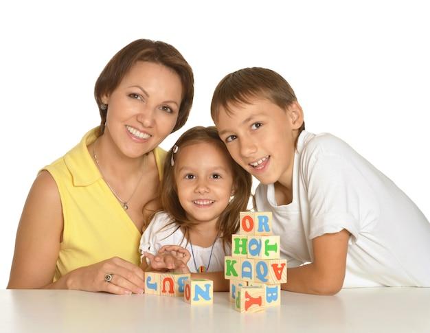 Moeder en haar kinderen spelen met kubussen geïsoleerd op wit