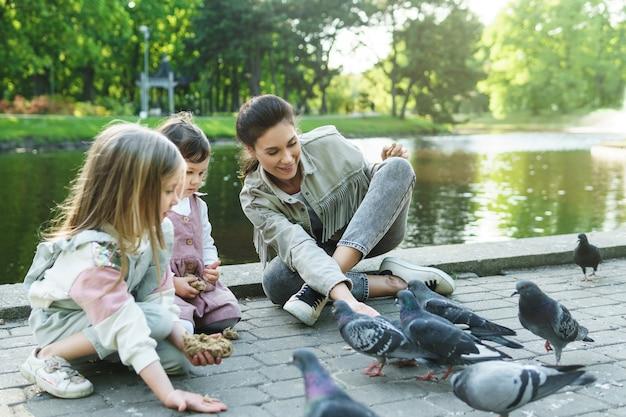 Moeder en haar kleine dochters voeden vogels in stadspark