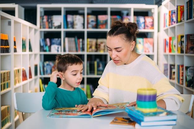 Moeder en haar kleine kind de kleuterzoon lezen samen kinderboeken