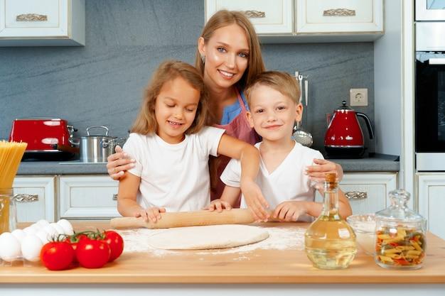 Moeder en haar kleine kinderen helpen haar deeg te bereiden