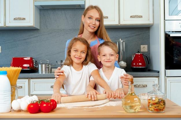 Moeder en haar kleine kinderen, jongen en meisje, die haar helpen deeg te bereiden