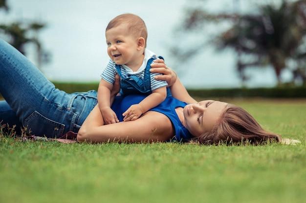 Moeder en haar kleine lachende zoon spelen samen, liggend gazon.