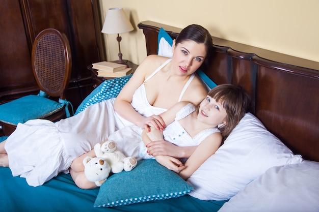 Moeder en haar schattige dochter liggen 's ochtends in bed nadat ze wakker zijn geworden en naar de camera kijken met een brede glimlach. studio opname