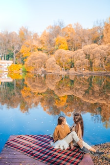 Moeder en haar schattige dochters genieten van herfstdag op het meer