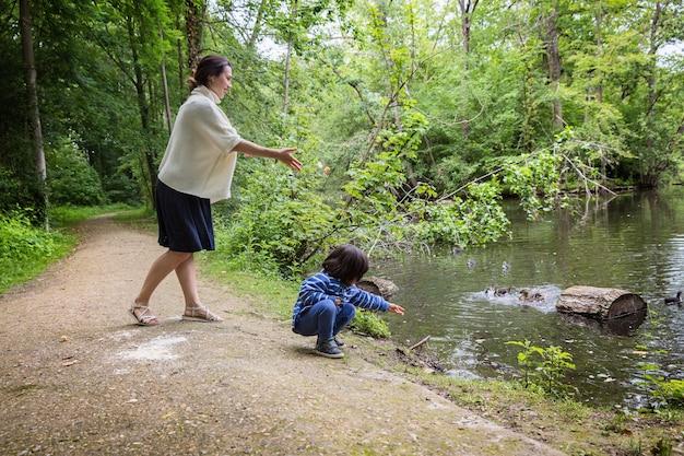 Moeder en haar schattige kleine kind voederen eenden in de vijver in een park. familie vrijetijdsbesteding