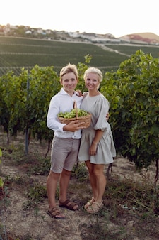 Moeder en haar tienerzoon staan in een wijngaard met een rieten mand en groene druiven in de natuur