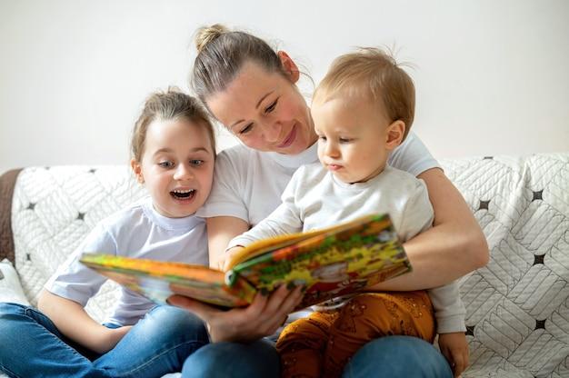 Moeder en haar twee kinderen lezen thuis op een bank een boek. blij en lachend