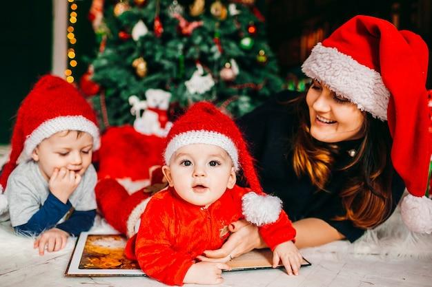 Moeder en haar zonen in rode hoeden liggen voor de kerstboom