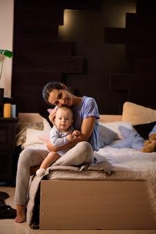 Moeder en haar zoon kind meisje spelen en knuffelen op het bed