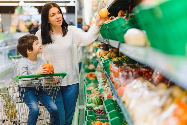Moeder en haar zoon kopen fruit op een boerenmarkt