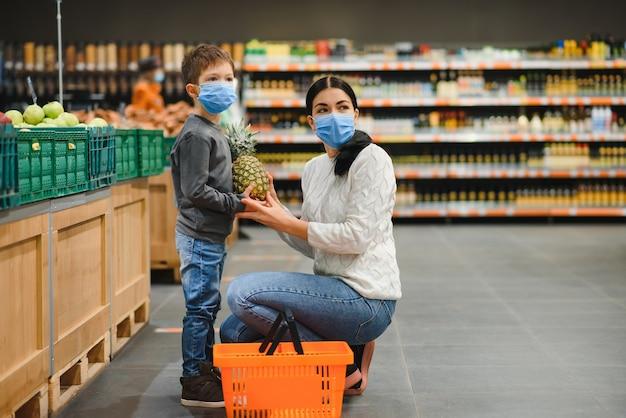 Moeder en haar zoon met beschermend gezichtsmasker winkelen in een supermarkt tijdens de coronavirus-epidemie