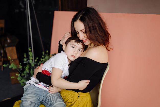 Moeder en haar zoon poseren in de studio en dragen vrijetijdskleding