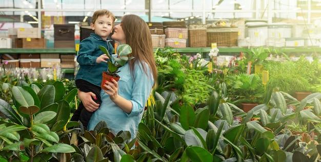 Moeder en haar zoontje in een plantenwinkel kiezen planten. tuinieren in serre. botanische tuin, bloementeelt, tuinbouwconcept