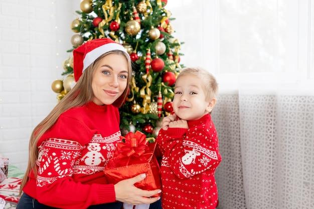 Moeder en haar zoontje in een rode trui en hoeden geven thuis cadeaus onder de kerstboom en verheugen zich in het nieuwe jaar en kerstmis