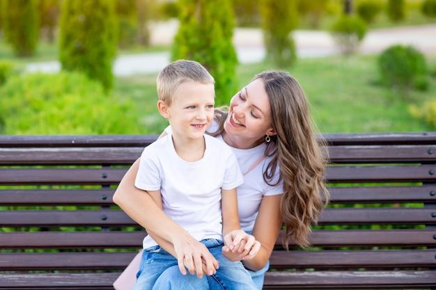 Moeder en haar zoontje in het park op een bankje in de zomer veel plezier met knuffelen, lachen en spelen