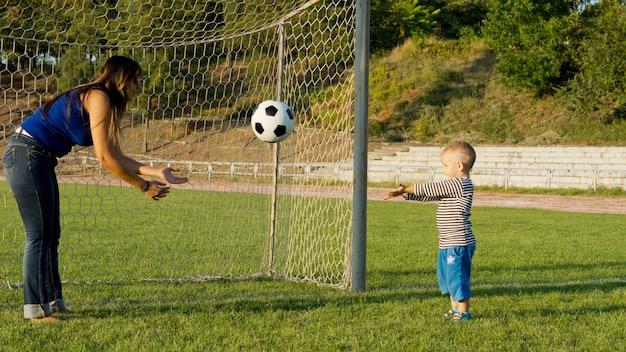 Moeder en haar zoontje staan voor doelpalen op een groen gras sportveld en gooien een voetbal naar elkaar