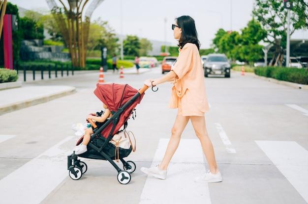 Moeder en het zoontje op de kinderwagen steken de weg over