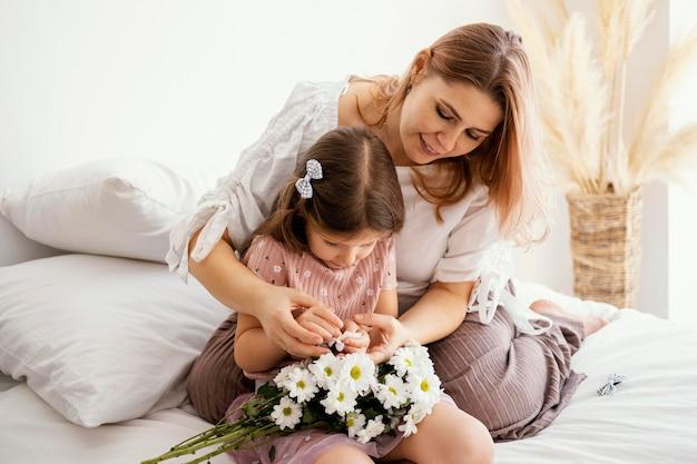 Moeder en jonge dochter boeket van lentebloemen houden