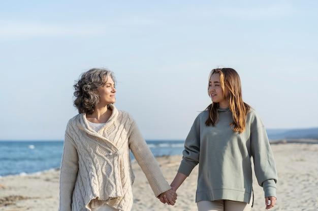 Moeder en jonge dochter brengen samen tijd door op het strand