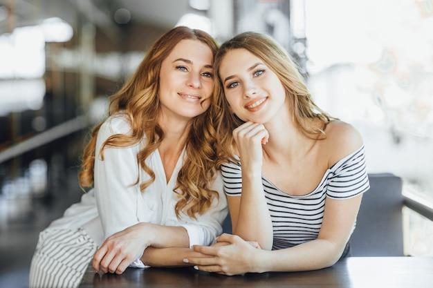 Moeder en jonge mooie dochter op een zomerterras