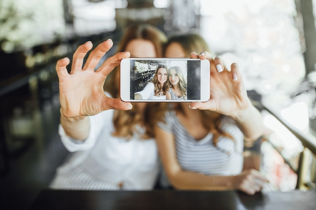 Moeder en jonge mooie tienerdochter doen selfie op het zomerterras café in casual kleding.
