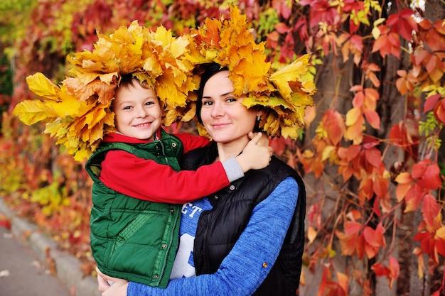 Moeder en jonge zoon dragen een kroon van gele bladeren knuffelen in de herfst park achtergrond glimlachen en kijken naar de camera.