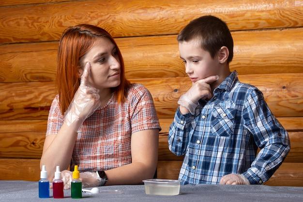 Moeder en jongen overwegen hoe ze thuis chemische experimenten zullen uitvoeren