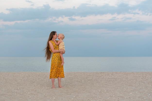 Moeder en kind aan zandstrand op zee en hemelachtergrond. moederlijke zorg en liefde. vakantie aan zee met baby.