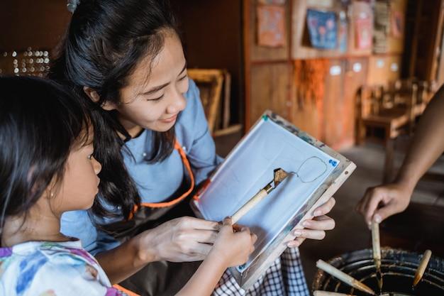 Moeder en kind aziaat die batikpatroon maken