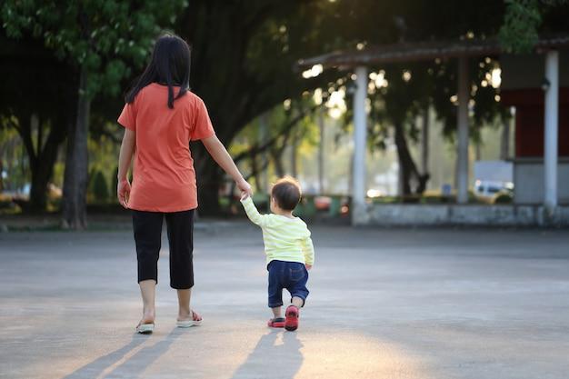 Moeder en kind die een hand houden om in het park te lopen.