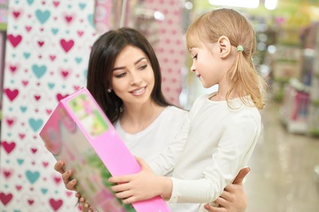 Moeder en kind die en stuk speelgoed in opslag kijken kiezen.