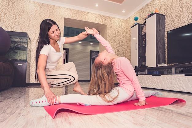 Moeder en kind-dochter doen yoga-oefeningen op de vloer in de kamer thuis. familie plezier binnenshuis met fitness. zelfisolatie in quarantaine tijdens een coronaviruspandemie. home entertainment.