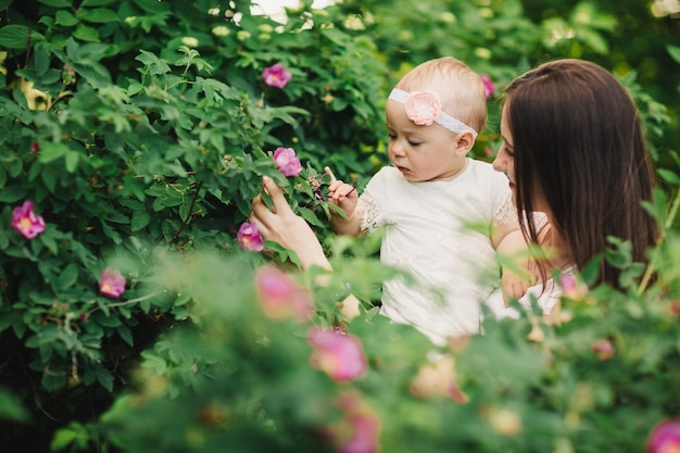 Moeder en kind dochter in lentetuin. jonge vrouw en babymeisje