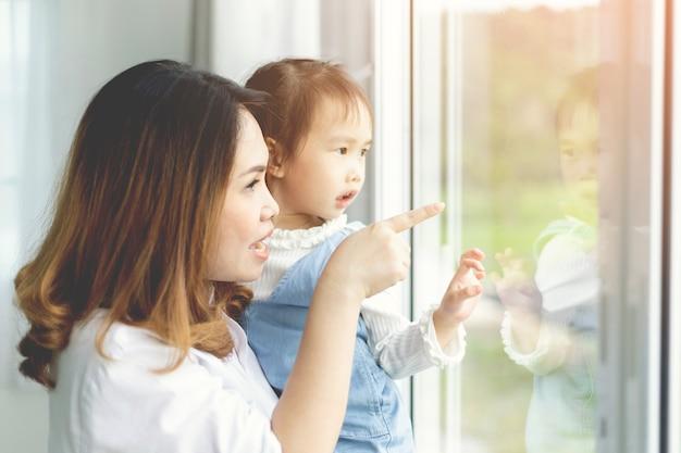 Moeder en kind dochter kijken uit het raam.