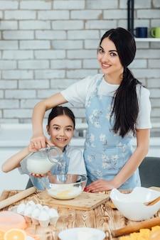 Moeder en kind dochter meisje koken koekjes en hebben plezier in de keuken