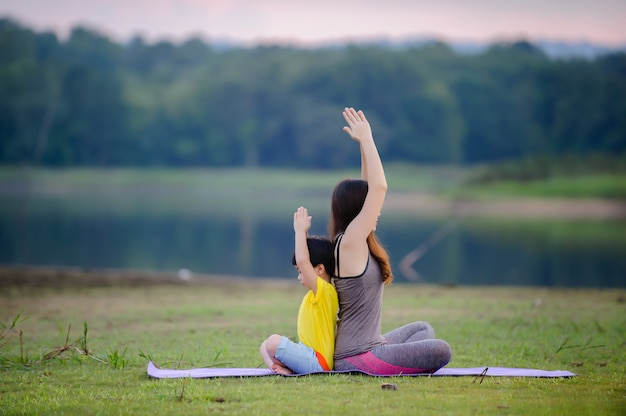 Moeder en kind doen yoga-oefeningen op gras in het park voor zonsondergang in de zomer.