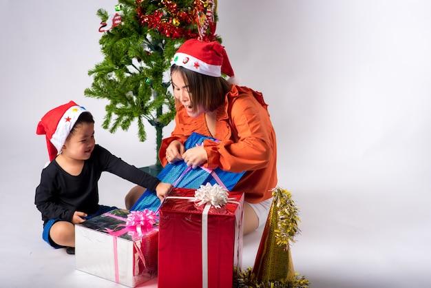 Moeder en kind erg blij met cadeau per dag kerstmis en gelukkig nieuwjaar op de achtergrond in de studio