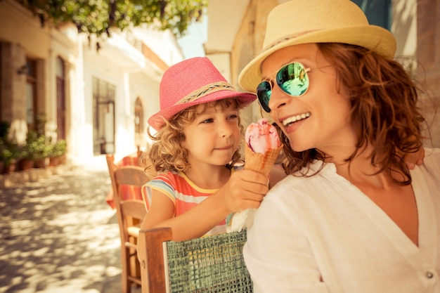 Moeder en kind eten van ijs in zomerterras buiten