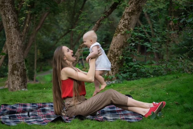 Moeder en kind genieten van een picknick in het park. moeder speelt met baby plezier en gelach