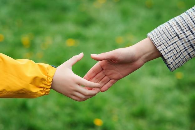 Moeder en kind handen reiken naar elkaar. steun, hulp en vertrouwen. ouder houdt de hand vast.