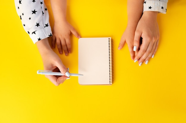 Moeder en kind handen schrijven in een notitieblok, bovenaanzicht