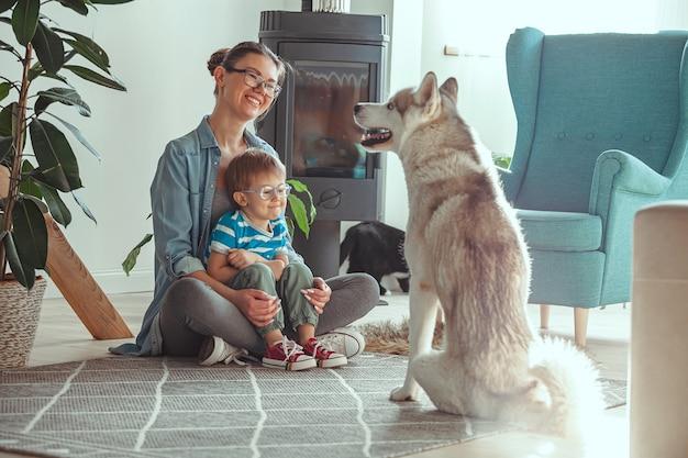 Moeder en kind hebben plezier en spelen thuis met de hond