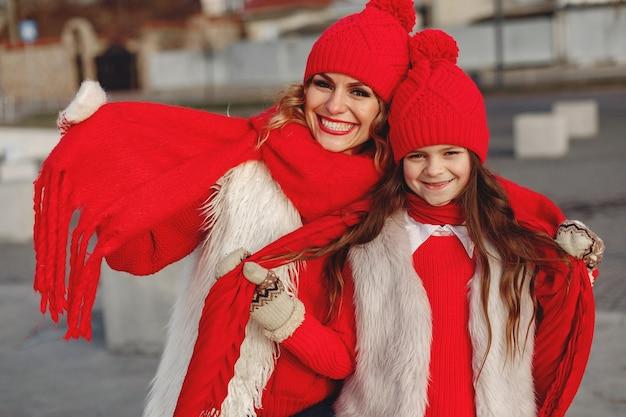 Moeder en kind in gebreide wintermutsen op familiekerstvakantie. handgemaakte wollen muts en sjaal voor mama en kind. breien voor kinderen. brei bovenkleding. vrouw en meisje in een park.