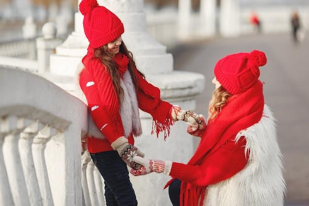 Moeder en kind in gebreide wintermutsen op familiekerstvakantie. handgemaakte wollen muts en sjaal voor mama en kind.