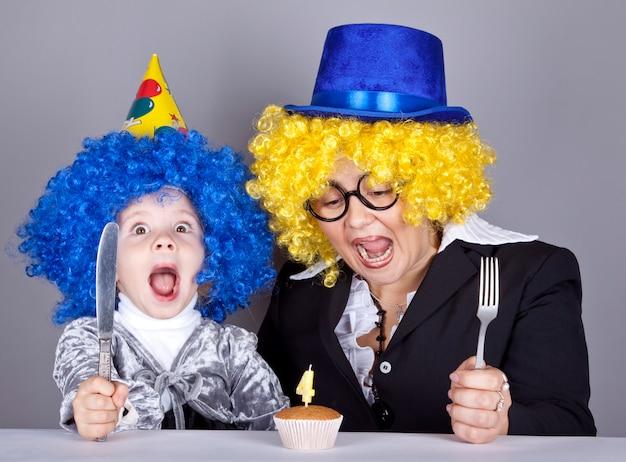 Moeder en kind in grappige pruiken en cake op verjaardag.