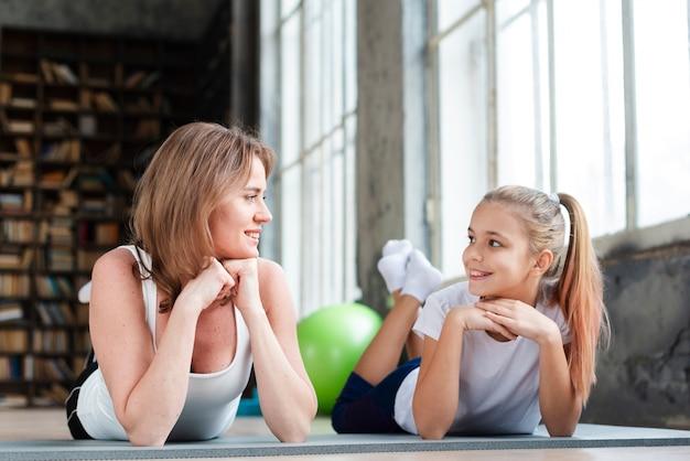 Moeder en kind kijken elkaar op yogamatten