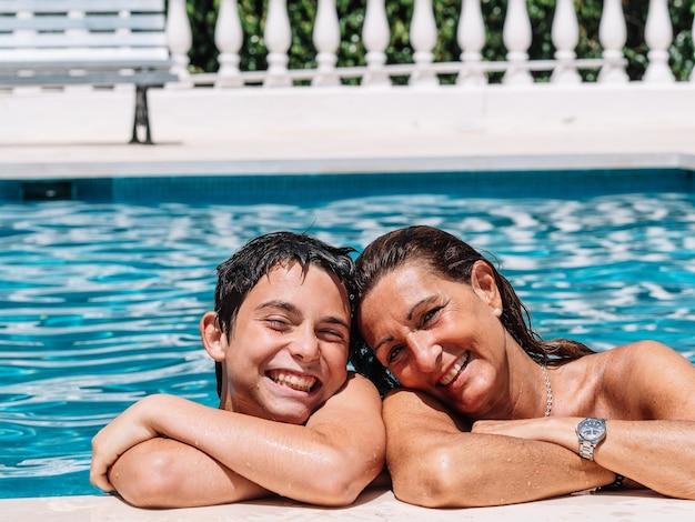 Moeder en kind liggen op een zonnige zomerdag in het zwembad en poseren liefdevol